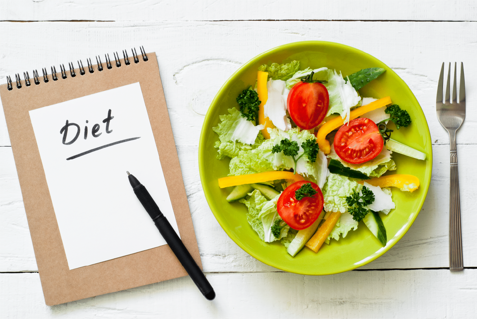 Plate of food next to a notebook that says diet