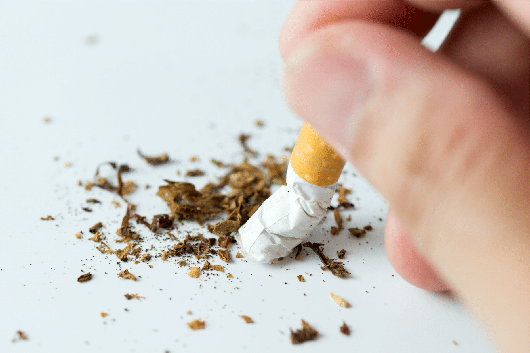 Crushing a cigarette on a white table
