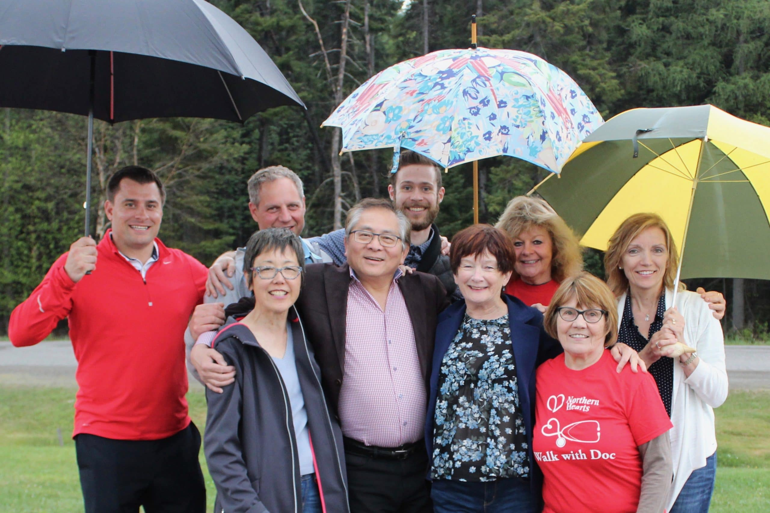 Group of people outside holding umbrellas and smiling