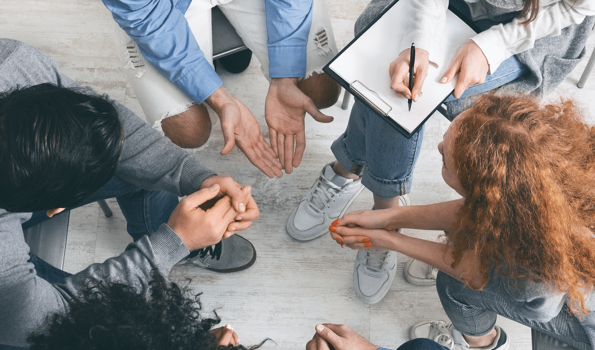 Diverse people sharing their problems at group therapy session, top view