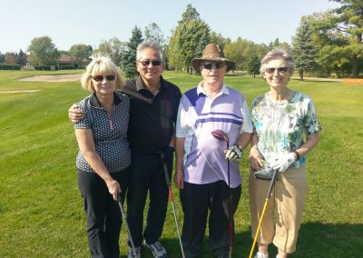 Doctor golfing with two women and one man