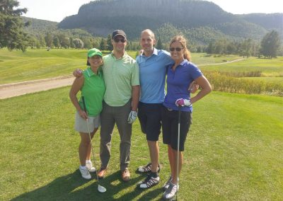 group of four golfing with Mount McKay in the background